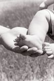 Parent retenant de petits pieds Photo libre de droits