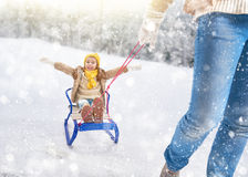 Parent rolls child on a sled Stock Photos