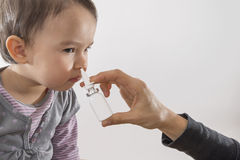 Parent's hand of a girl applies a nasal spray to her Stock Images