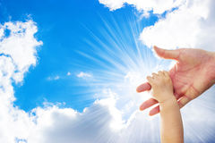 A one year old baby girl is grabbing her parent's hand, with a background of blue sky and white clouds. Sun shining Royalty Free Stock Photo