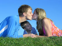 Parent's kiss and son. On blue sky stock images