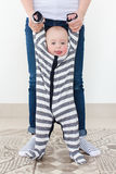 A parent supporting a child. Vertical indoors portrait of a little boy standing being held with a parent Stock Image