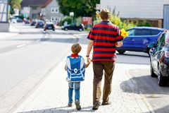 Young father taking child, kid boy to school on his first day. Parent taking child, kid boy to school. Pupil of primary school go study. Father holding hand of royalty free stock photography
