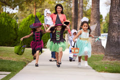 Parent Taking Children Trick Or Treating At Halloween Stock Photos