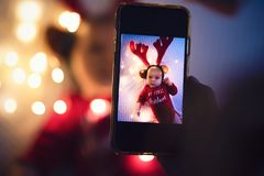Parent taking photo of a baby with smartphone. Digital family memories royalty free stock photo