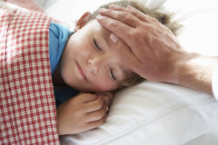 Parent Taking Temperature Of Young Boy Asleep In Bed Stock Photo