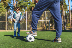 Parent teaching son to play football. Aspirated boy is playing football with his father with interest. Man is preparing to kick the ball to him Royalty Free Stock Image