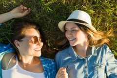 The parent and teenager, mom and 14 year old daughter are smiling lying on the green grass. view from above.  Stock Photo