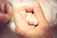 Parent tenir sa main nouveau-née de bébé symbolisant l'amour et le soin Photo libre de droits