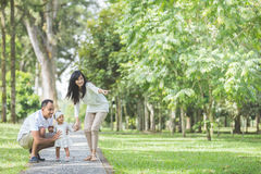 Parent with their cute baby in the park having fun together Royalty Free Stock Images