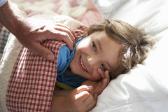 Parent Waking Young Boy Asleep In Bed Stock Photography