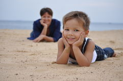 Parental Controls. Boy lying on the sand, watching him from afar mom Royalty Free Stock Photo