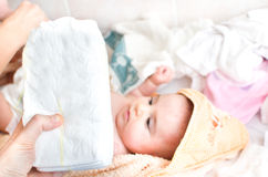 Parental hand holds stack of  diapers baby on changing table Royalty Free Stock Photo