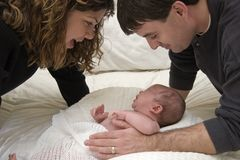 Parenthood. Mother and Father admiring their baby royalty free stock images