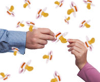 Parenthood concept. Close up of hands and falling pacifiers as parenthood concept Stock Photos