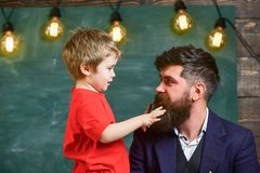 Parenthood concept. Little boy telling something to his dad. Daddy looking at son while kid is playing with his beard. Man and child sideview Stock Image