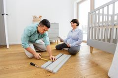 Family couple assembling baby bed at home. Parenthood, family and nursery concept - happy middle-aged men and his pregnant wife user manual and ruler assembling royalty free stock photography