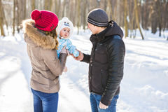 Parenthood, fashion, season and people concept - happy family with baby in winter clothes outdoors Royalty Free Stock Photography