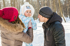 Parenthood, fashion, season and people concept - happy family with baby in winter clothes outdoors Stock Photos
