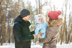 Parenthood, fashion, season and people concept - happy family with baby in winter clothes outdoors Royalty Free Stock Photos