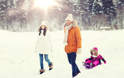 Happy family with sled walking in winter forest Royalty Free Stock Images