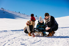 Parenthood, fashion, season and people concept - happy family with child on sled walking in winter outdoors.  Stock Photography