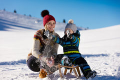 Parenthood, fashion, season and people concept - happy family with child on sled walking in winter outdoors Royalty Free Stock Images