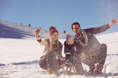Parenthood, fashion, season and people concept - happy family with child on sled walking in winter outdoors Royalty Free Stock Image