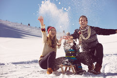 Parenthood, fashion, season and people concept - happy family with child on sled walking in winter outdoors Stock Images