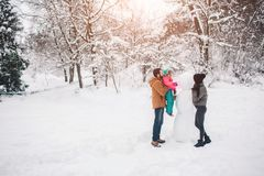 Parenthood, fashion, season and people concept - happy family with child in winter clothes outdoors Stock Photo