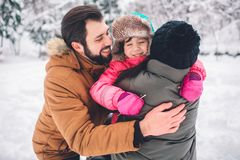 Parenthood, fashion, season and people concept - happy family with child in winter clothes outdoors Royalty Free Stock Photography