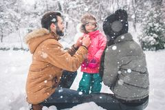 Parenthood, fashion, season and people concept - happy family with child in winter clothes outdoors Stock Photography