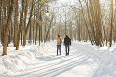 Parenthood, fashion, season and people concept - happy family with child in winter clothes walking outdoors. Stock Photos