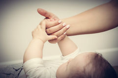 Parenthood. Mother and her little baby touching each other hands Royalty Free Stock Photo