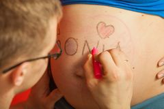 Pregnant woman belly, father drawing on it Stock Photography