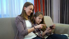 Parenting family pastime home mother daughter. Parenting time. calm family pastime. home cosy atmosphere. mother and daughter watching video on smartphone Stock Photo