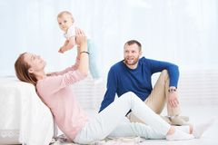 Parenting family. Mother and father playing with little newborn baby. Parenting and family. Woman with men with little newborn baby in bed royalty free stock images
