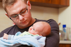 Father holding taking care of newborn baby Stock Photos