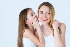 Parenting loving family relationship whisper. Good parenting and loving family relationships. daughter whispering a secret into her mothers ear Royalty Free Stock Photo