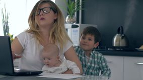 Parenting, mum com o bebê em seus braços discute seu filho que interfere com o trabalho na cozinha vídeos de arquivo