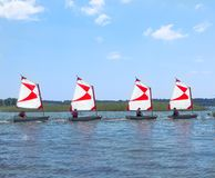 PARENTIS-EN-BORN, FRANCE - JULY 25, 2018: Four dinghy with a red-white sails on the lake. Sailboats go in a dense state royalty free stock photos