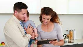 Parents à l'aide du PC de comprimé tandis que le père tient le bébé banque de vidéos