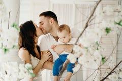 Parents étreignant leur fils et baisers de bébé photographie stock