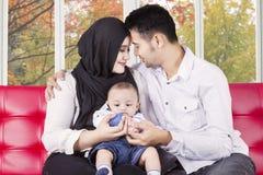 2 parents владения их сын на кресле Стоковая Фотография
