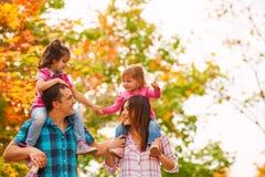 Parents мама, папа снесите маленькие девочек на плечах стоковые фото