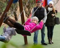 Parents отбрасывая дети на парке Стоковые Изображения