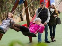 Parents отбрасывая дети на парке Стоковая Фотография