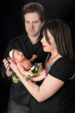 Parents Admiring Newborn. Mom holding her newborn daughter with dad looking on.  On a black background Stock Image