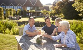 Parents With Adult Offspring Enjoying Outdoor Summer Drink At Pub royalty free stock images