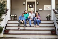 Parents With Adult Offspring Sitting On Steps in Front Of House stock photos